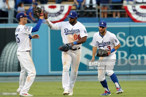Cody Bellinger Yasiel Puig and Chris Taylor of the Los Angeles Dodgers celebrate after winning Game 5 of the NLCS against the Milwaukee Brewers at...