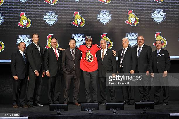 Cody Ceci 15th overall pick by the Ottawa Senators poses on stage with NHL Commissioner Gary Bettman and Senators representatives during Round One of...