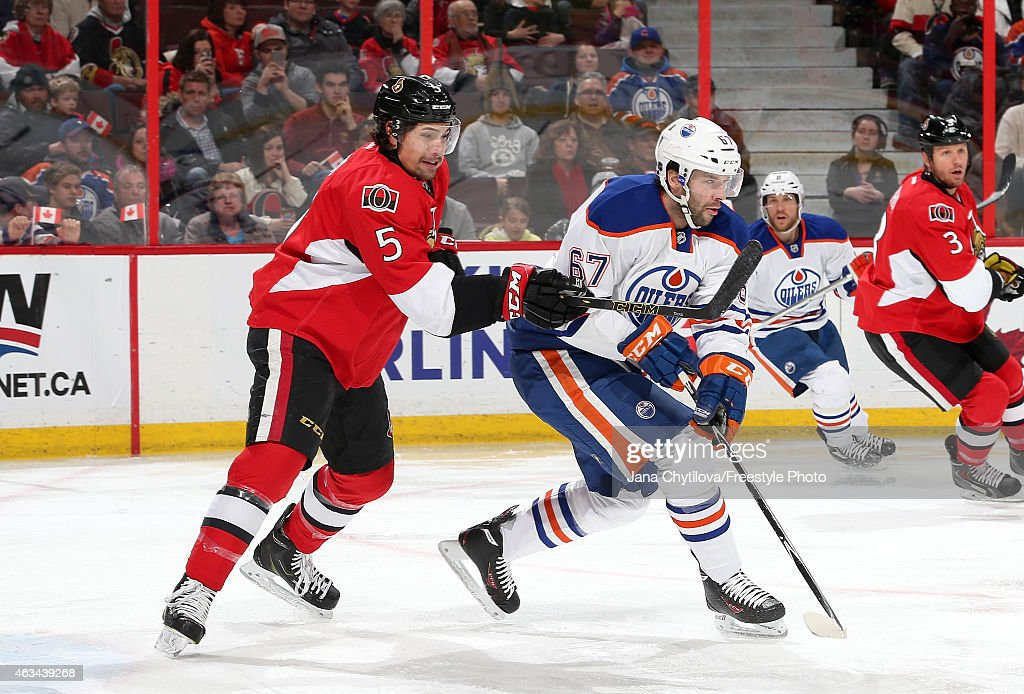 Cody Ceci #5 of the Ottawa Senators defends against Benoit Pouliot #67 of the Edmonton Oilers in the first period at Canadian Tire Centre on February 14, 2015 in Ottawa, Ontario, Canada.