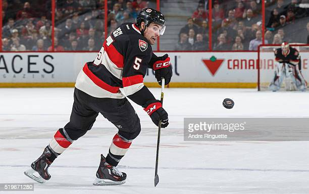 Cody Ceci of the Ottawa Senators keeps the puck alive as he flips it back into the offensive zone during an NHL game against the Florida Panthers at...
