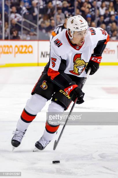 Cody Ceci of the Ottawa Senators plays the puck down the ice during third period action against the Winnipeg Jets at the Bell MTS Place on February...
