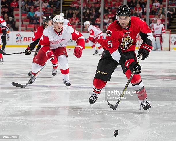 Cody Ceci of the Ottawa Senators skates after a loose puck in front of Justin Abdelkader of the Detroit Red Wings during an NHL game at Joe Louis...