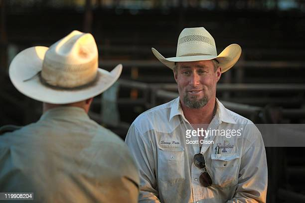 Cody Cochran and Sonny Pate take a break from moving cattle into a pen prior to their being offered for sale at the Abilene Livestock Auction July 26...