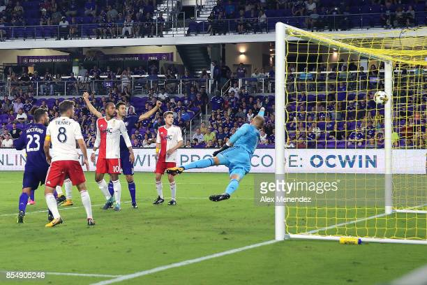 Cody Cropper of New England Revolution dives to block a shot attempt as Sebastian Hines of Orlando City SC scores a goal during a MLS soccer match at...