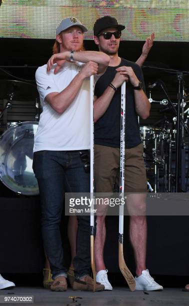 Cody Eakin and Shea Theodore of the Vegas Golden Knights rest on hockey sticks as they watch their teammates being introduced during the team's...