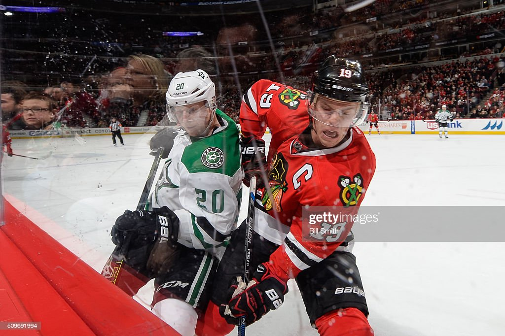 Cody Eakin #20 of the Dallas Stars and Jonathan Toews #19 of the Chicago Blackhawks work to get the puck away from the boards in the third period of the NHL game at the United Center on February 11, 2016 in Chicago, Illinois.
