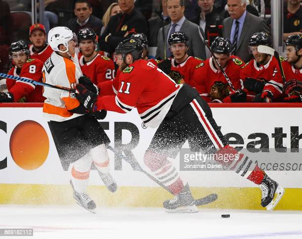Cody Franson of the Chicago Blackhawks hits Travis Konecny of the Philadelphia Flyers at the United Center on November 1, 2017 in Chicago, Illinois.