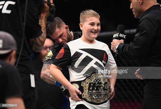 Cody Garbrandt places the UFC title belt around a young fan's wasit after defeating Dominick Cruz in their UFC bantamweight championship bout during...