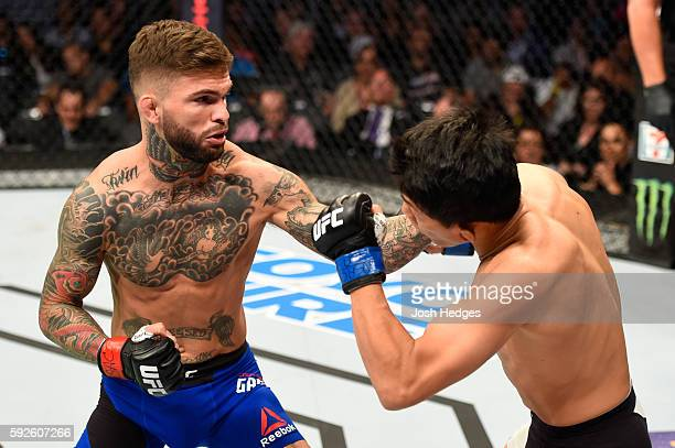 Cody Garbrandt punches Takeya Mizugaki of Japan in their bantamweight bout during the UFC 202 event at T-Mobile Arena on August 20, 2016 in Las...