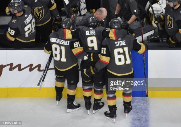 Cody Glass of the Vegas Golden Knights is helped off the ice by teammates Jonathan Marchessault and Mark Stone after suffering an injury during the...