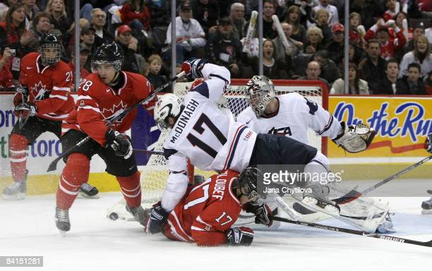 Cody Goloubef of Team Canada goes down on the ice as Ryan McDonagh of Team USA falls on top of him and Patrice Cormier of Team Canada and Thomas...