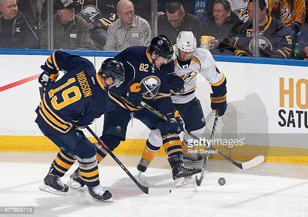 Cody Hodgson and Marcus Foligno of the Buffalo Sabres fight for puck control against Ryan Ellis of the Nashville Predators at First Niagara Center on...