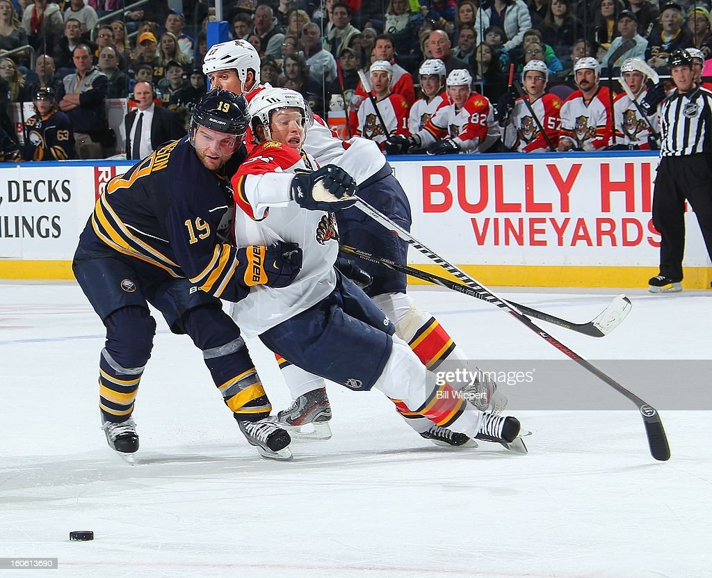 Cody Hodgson #19 of the Buffalo Sabres battles for the puck against Brian Campbell #51 and Filip Kuba #17 of the Florida Panthers on February 3, 2013 at the First Niagara Center in Buffalo, New York.