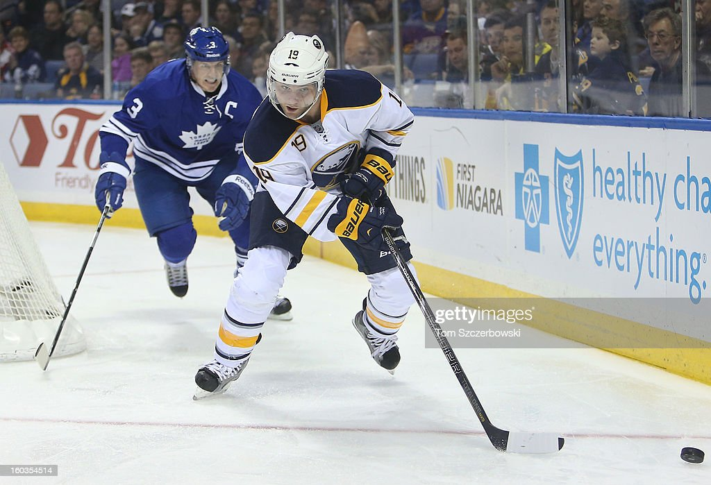 Cody Hodgson #19 of the Buffalo Sabres chases the puck as Dion Phaneuf #3 of the Toronto Maple Leafs follows in NHL action at First Niagara Center on January 29, 2013 in Buffalo, New York.