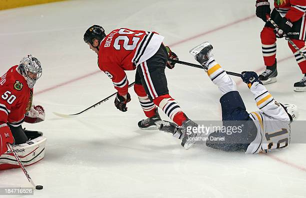 Cody Hodgson of the Buffalo Sabres hits the ice after colliding with Bryan Bickell of the Chicago Blackhawks as Corey Crawford makes a save at the...