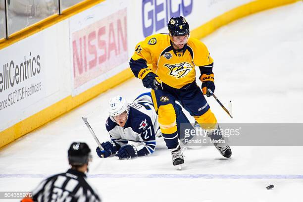 Cody Hodgson of the Nashville Predators skates with the puck as Nikolaj Ehlers of the Winnipeg Jets hits the ice during a NHL game at Bridgestone...