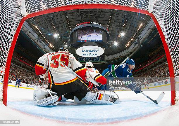 Cody Hodgson of the Vancouver Canucks flies through the crease in front of Henrik Karlsson of the Calgary Flames during an NHL game at Rogers Arena...