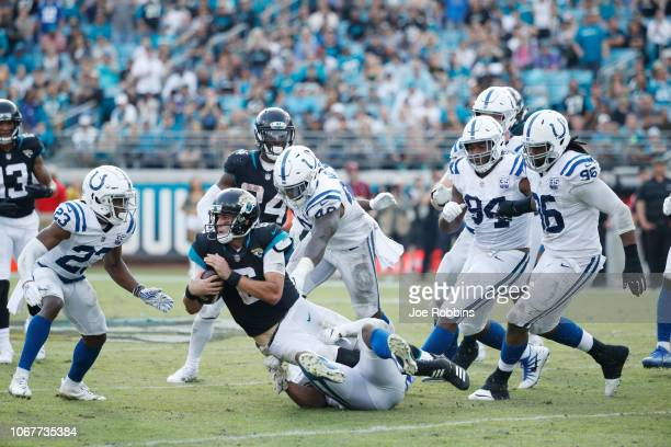 Cody Kessler of the Jacksonville Jaguars is tackled by a group of Indianapolis Colts defenders during their game at TIAA Bank Field on December 2...