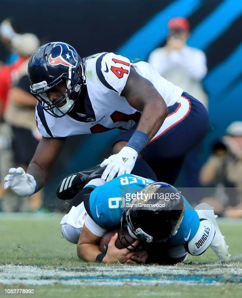 Cody Kessler of the Jacksonville Jaguars is tackled by Zach Cunningham of the Houston Texans during the game at TIAA Bank Field on October 21 2018 in...