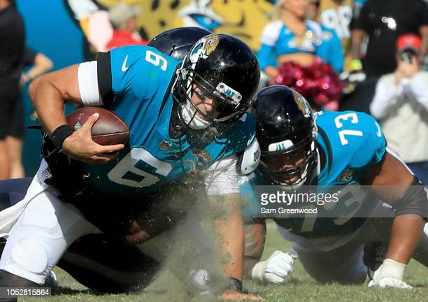 Cody Kessler of the Jacksonville Jaguars is tackled during the game against the Houston Texans at TIAA Bank Field on October 21 2018 in Jacksonville...