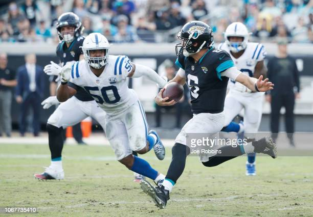 Cody Kessler of the Jacksonville Jaguars runs with the football in front of Anthony Walker of the Indianapolis Colts during their game at TIAA Bank...