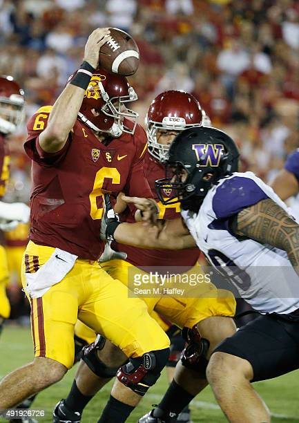 Cody Kessler of the USC Trojans eludes the tackle of Taniela Tupou of the Washington Huskies during the second half of a game at Los Angeles Memorial...