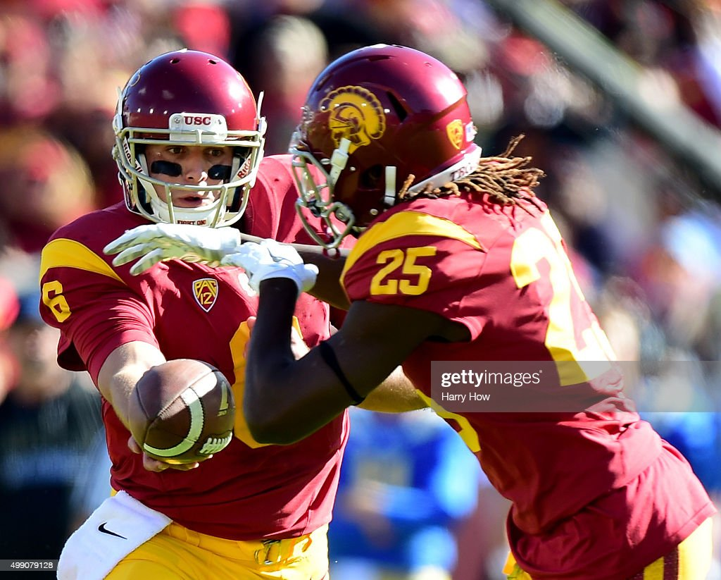 Cody Kessler #6 of the USC Trojans hands off to Ronald Jones II #25 during a 40-21 win over the UCLA Bruins at Los Angeles Memorial Coliseum on November 28, 2015 in Los Angeles, California.