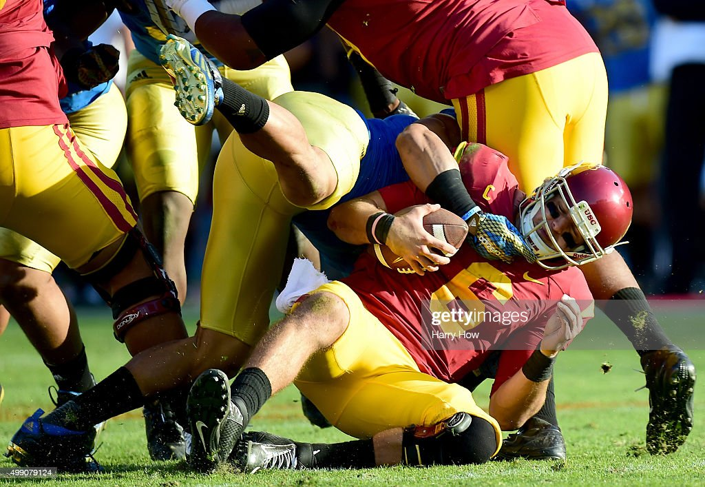 Cody Kessler #6 of the USC Trojans is sacked by Aaron Wallace #51 of the UCLA Bruins during the third quarter at Los Angeles Memorial Coliseum on November 28, 2015 in Los Angeles, California.