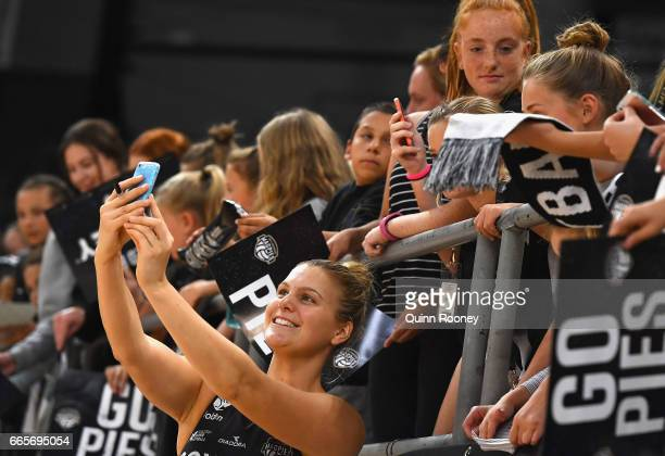 Cody Lange of the Magpies poses for selfies with fans during the round eight Super Netball match between the Magpies and Fever at Hisense Arena on...
