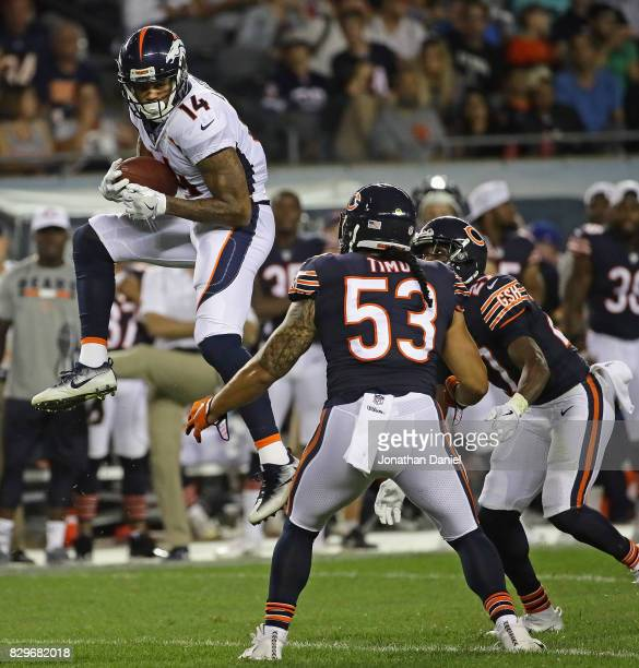 Cody Latimer of the Denver Broncos catches a pass over John Timu and Sherrick McManis of the Chicago Bears during a preseason game at Soldier Field...