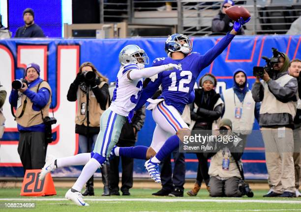 Cody Latimer of the New York Giants makes a first down reception under pressure from Anthony Brown of the Dallas Cowboys during the fourth quarter at...