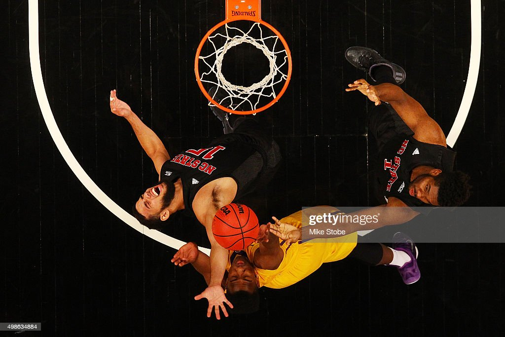 Cody Martin #15 and Lennard Freeman #1 of the North Carolina State Wolfpack battle for the ball against Elbert Robinson III #3 of the LSU Tigers at Barclays Center on November 24, 2015 in Brooklyn borough of New York City.