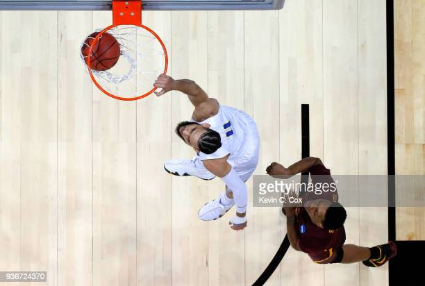Cody Martin of the Nevada Wolf Pack dunks against Cameron Satterwhite of the Loyola Ramblers in the first half during the 2018 NCAA Men's Basketball...