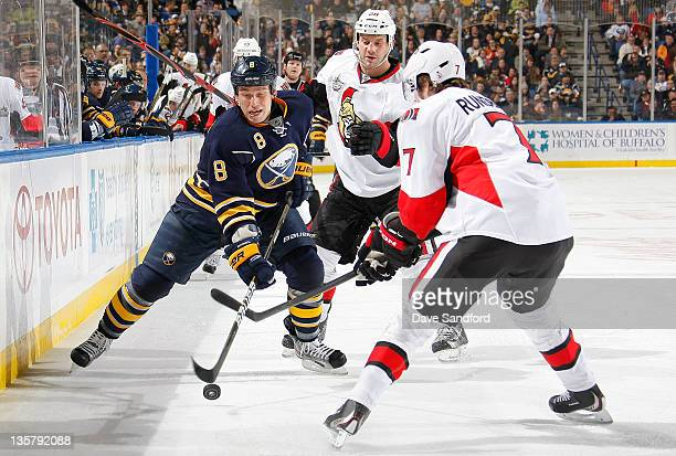 Cody McCormick of the Buffalo Sabres carries the puck as both David Rundblad and Zenon Konopka of the Ottawa Senators defend during their NHL game at...