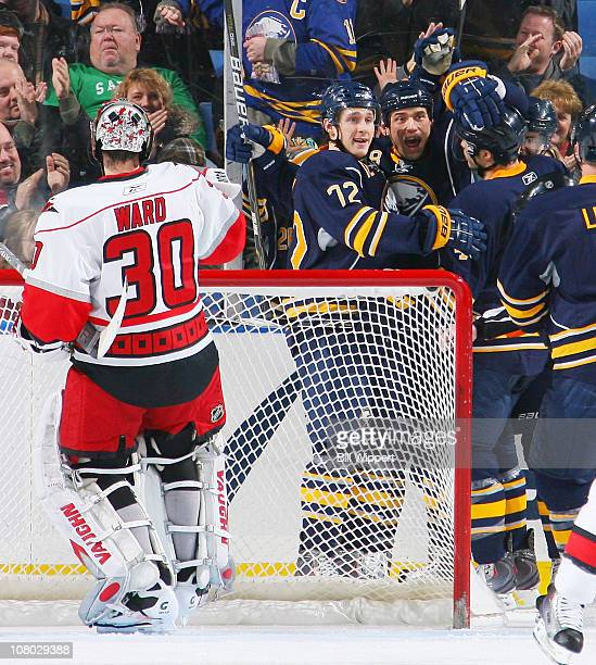 Cody McCormick of the Buffalo Sabres celebrates his second period goal with Luke Adam behind goaltender Cam Ward of the Carolina Hurricanes at HSBC...