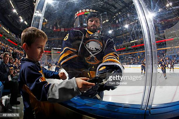 Cody McCormick of the Buffalo Sabres hands a puck to Lawson Zlotek during warmups before the start of a game against the Ottawa Senators at the First...