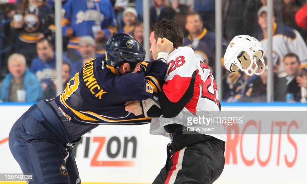 Cody McCormick of the Buffalo Sabres lands a punch on Zenon Konopka of the Ottawa Senators knocking off his helmet during the first period at First...