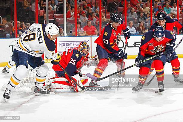 Cody McCormick of the Buffalo Sabres looks for a tip in as Kris Versteeg assists goaltender Jacob Markstrom of the Florida Panthers defend the net at...