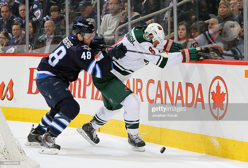 Cody McCormick #8 of the Minnesota Wild protects the puck from Carl Klingberg #48 of the Winnipeg Jets along the boards during third-period action at the MTS Centre on April 7, 2014 in Winnipeg, Manitoba, Canada.