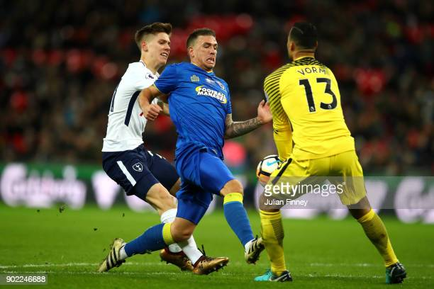 Cody McDonald of AFC Wimbledon is chased down by Juan Foyth and Michel Vorm of Tottenham Hotspur during The Emirates FA Cup Third Round match between...