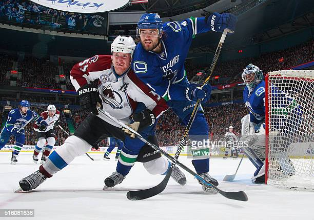 Cody McLeod of the Colorado Avalanche and Christopher Tanev of the Vancouver Canucks battle for position beside Ryan Miller of the Canucks during...