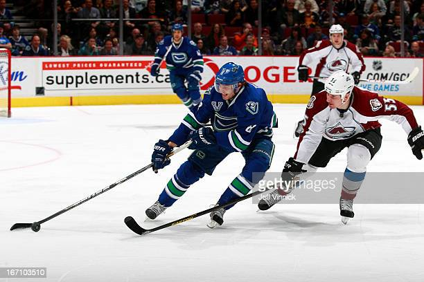 Cody McLeod of the Colorado Avalanche checks Christopher Tanev of the Vancouver Canucks during an NHL game at Rogers Arena March 28 2013 in Vancouver...