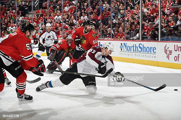 Cody McLeod of the Colorado Avalanche dives toward the puck against Brandon Mashinter and Erik Gustafsson of the Chicago Blackhawks in the second...