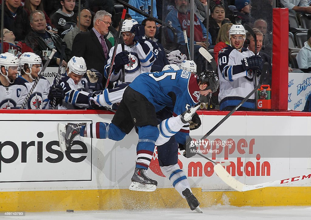 Cody McLeod #55 of the Colorado Avalanche hits a member of the Winnipeg Jets at the Pepsi Center on December 29, 2013 in Denver, Colorado. The Jets defeated the Avalanche 2-1 in overtime.