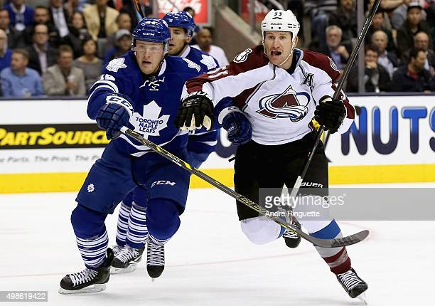 Cody McLeod of the Colorado Avalanche plays against Morgan Rielly of the Toronto Maple Leafs at the Air Canada Center on October 14 2014 in Toronto...
