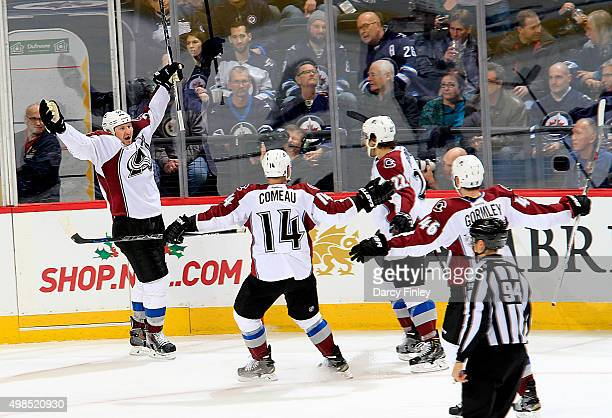 Cody McLeod of the Colorado Avalanche throws his arms up and celebrates after scoring a third period goal against the Winnipeg Jets with teammates...