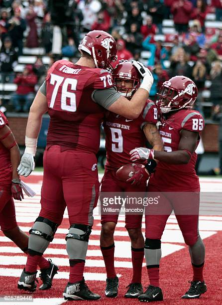 Cody O'Connell and John Thompson of the Washington State Cougars congratulate teammate Gabe Marks after his touchdown against the Washington Huskies...