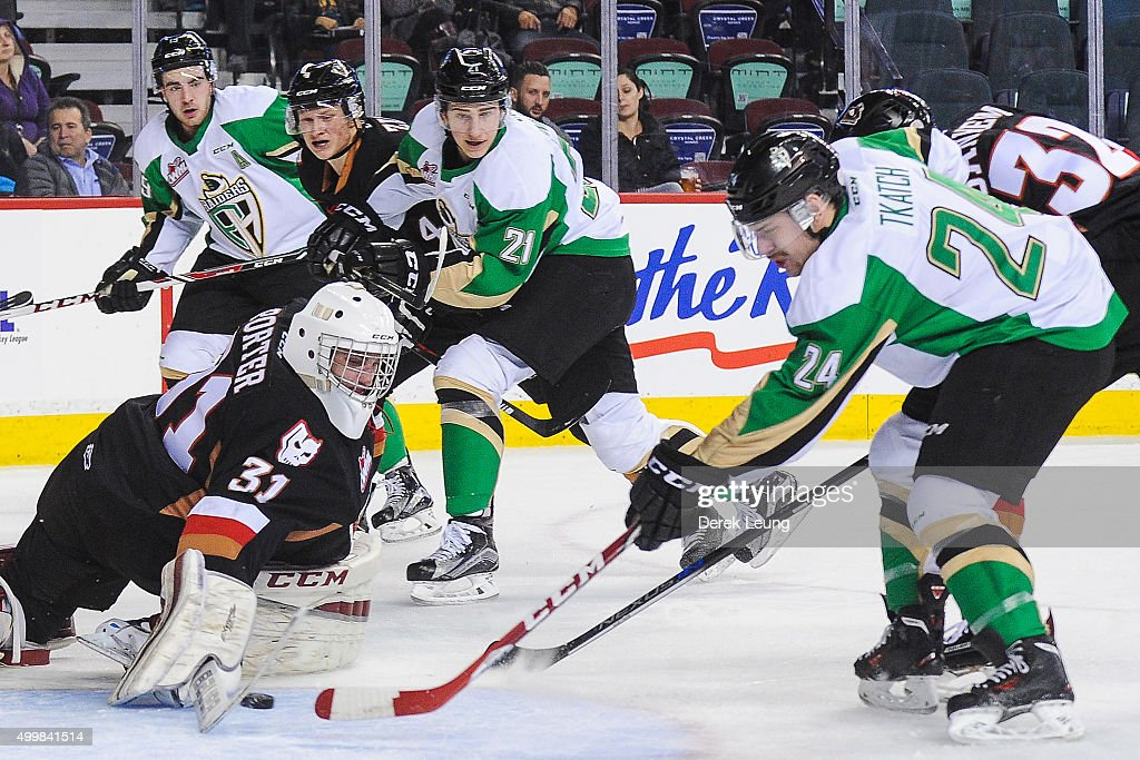 Cody Porter #31 of the Calgary Hitmen makes a save against Jordan Tkatch #24 of the Prince Albert Raiders during a WHL game at Scotiabank Saddledome on December 3, 2015 in Calgary, Alberta, Canada.