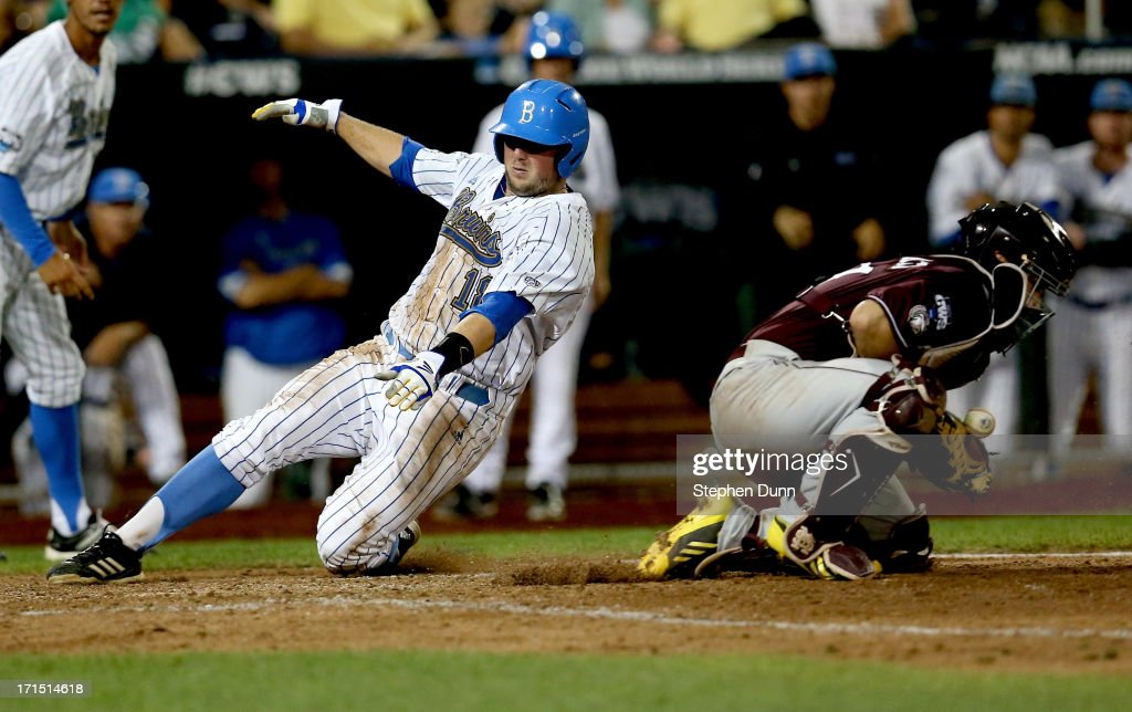 Cody Regis #18 of the UCLA Bruins slides into home to score a run ahead of the throw to catcher Nick Ammirati #17 of the Mississippi State Bulldogs in the sixth inning during game two of the College World Series Finals on June 25, 2013 at TD Ameritrade Park in Omaha, Nebraska.