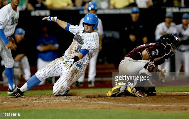 Cody Regis of the UCLA Bruins slides into home to score a run ahead of the throw to catcher Nick Ammirati of the Mississippi State Bulldogs in the...